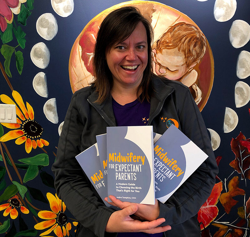 photo of Aubre smiling holding five copies of her book